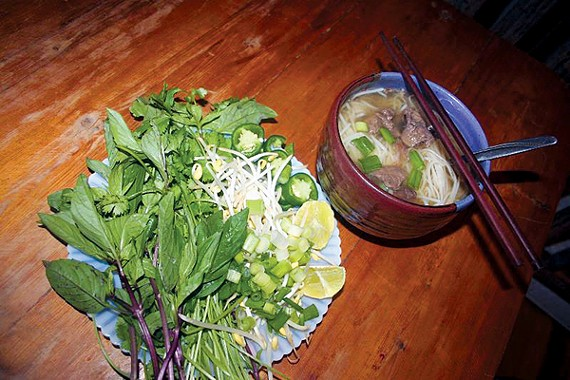 Pho, served with a salad of herbs and sprouts for garnish