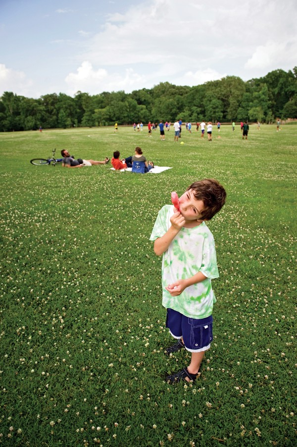 Pip Borden, 9, enjoys a popsicle during a hot afternoon on the Greensward at Overton Park. - BRANDON DILL