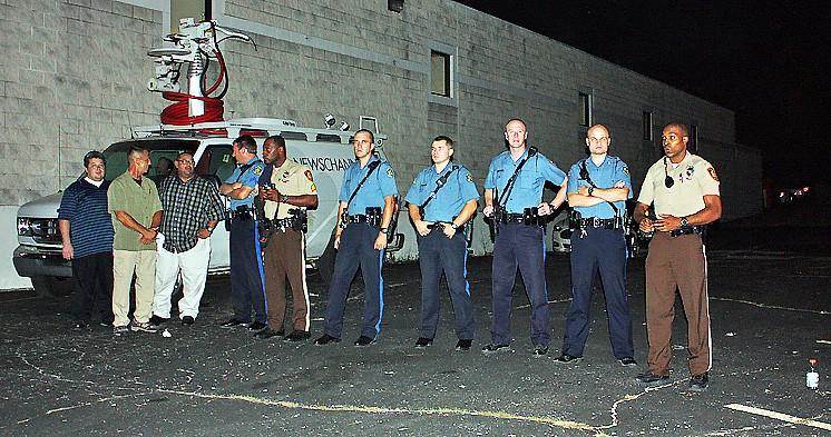 Police guarding a news truck on West Florissant - DOUG GILLON
