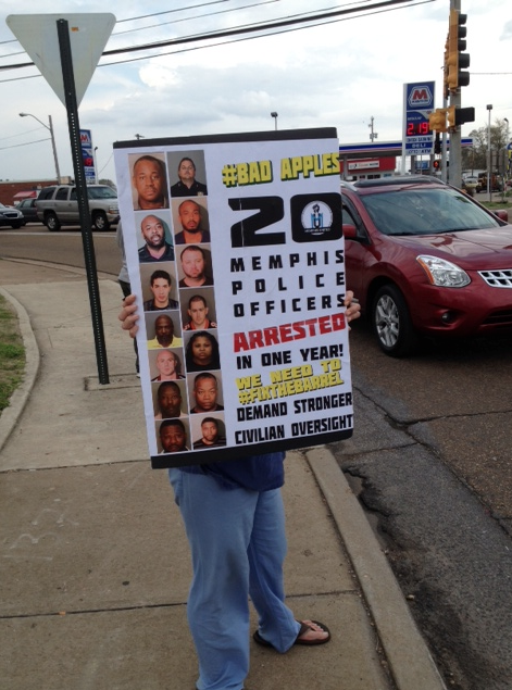 A woman holds a sign displaying several Memphis Police officers who have been arrested since 2014 at the intersection of Lamar and Airways. - LOUIS GOGGANS