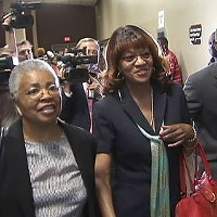 Still wearing the same odd smile she had when turning herself in Thursday night, Brooks, acconpanied by an unidentified supporter (left) and her attorney, Andre Wharton, prepared to enter the courtroom of General Sessions Judge Bill Anderson, Jr.