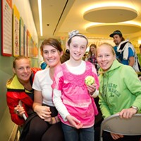 """Tennis players surround """"Maddie,"""" a patient at St. Jude."""