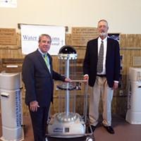 TRU-D president Chuck Dunn and inventor Jeffrey Deal with a germ-killing robot.