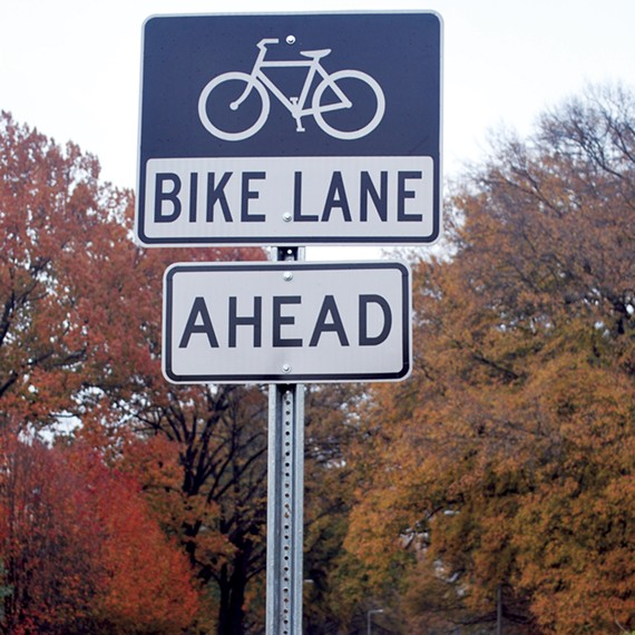 Two bike lane signs are positioned only a few feet apart on Central Avenue.