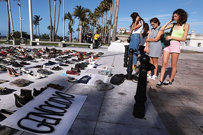People look at hundreds of pairs of shoes displayed at the Capitol to pay tribute to Hurricane Maria's victims after a research team led by Harvard University estimated that 4,645 people lost their lives, a number not confirmed by the government, in San Juan, Puerto Rico, June 1, 2018. - REUTERS   ALVIN BAEZ