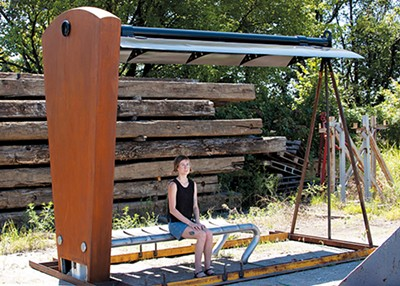 """Eva Langsdon sits under """"Synergy,"""" a bus shelter by metalsmith Lewis Body."""