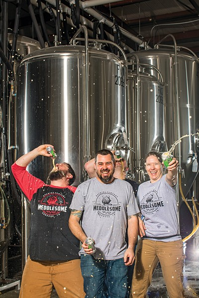 Cheers to these meddling kids! (l-r) Richie EsQuivel, Ben Pugh, brewer Amber Rogers, and volunteer Larry Stone (back) celebrate Meddlesome Brewing Company's three-peat victory in Memphis Flyer's Beer Bracket Challenge.