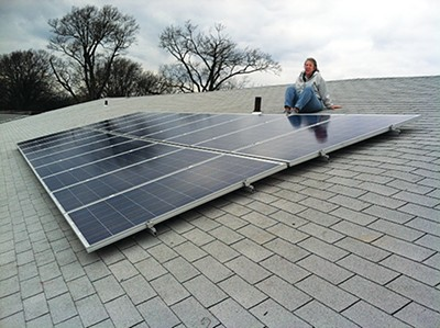 Julia Hicks poses with First Congregational Church's solar array. - LAURA JEAN HOCKING