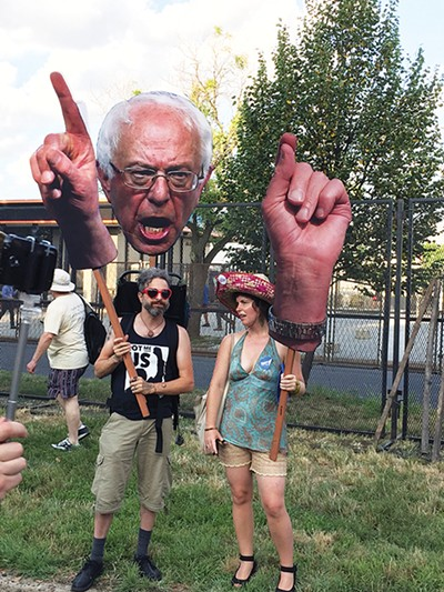 Protesters hold aloft a larger-than-life Sanders cutout outside the Wells Fargo Center in Philadelphia. - CHRIS DAVIS