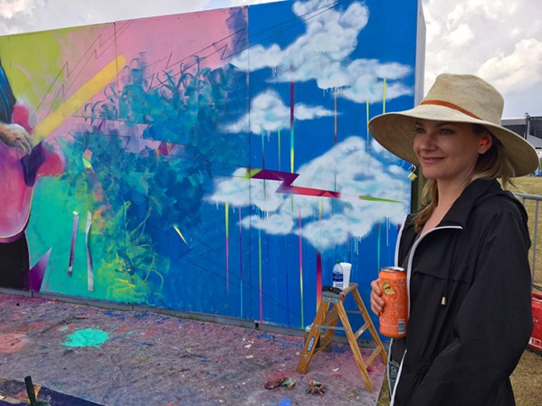 Artist Lauren Lazaru takes a break from working on the mural she and Curtis Glover created live on the festival grounds. - CHRIS MCCOY