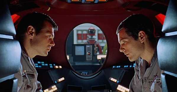 Astronauts Frank Poole (Gary Lockwood) and David Bowman (Keir Duella) discuss the fate of their sentient computer crewmate HAL 9000. This composition is a reference to a shot from Citizen Kane.
