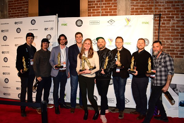 Winning filmmakers on the red carpet at the 2019 Oxford Film Festival, (left to right) John Charter, Paul Kaiser, Timothy Blackwood, Bradford Downs, Suzannah Herbert, Morgan Jon Fox, John Rash, Will Stewart, and Christian Walker - JOEY BRENT
