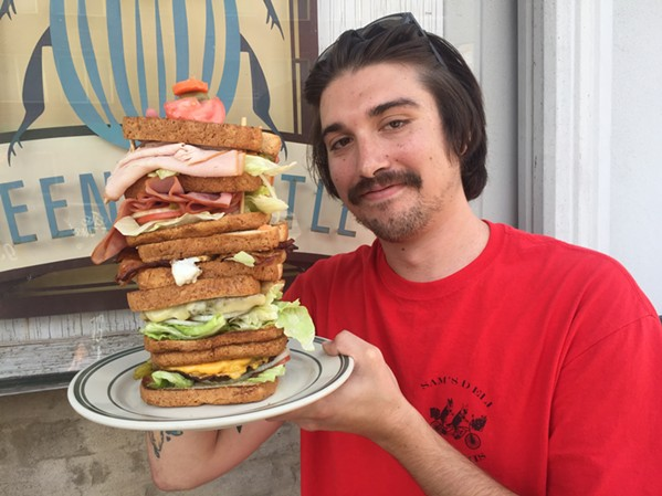 """Ryan Joseph Hopgood of Memphis Sandwich Clique loves sandwiches. He's holding a """"Dagwood"""" style sandwich The Green Beetle made up for fun. Note: They don't sell these at The Green Beetle. - MICHAEL DONAHUE"""