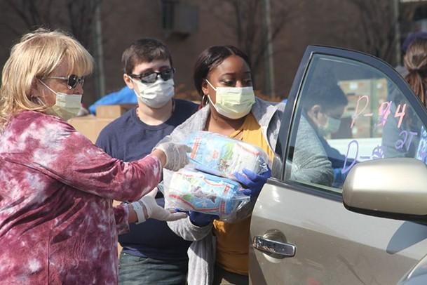 Volunteers load food into a car at a mobile food pantry. - FACEBOOK/MID-SOUTH FOOD BANK