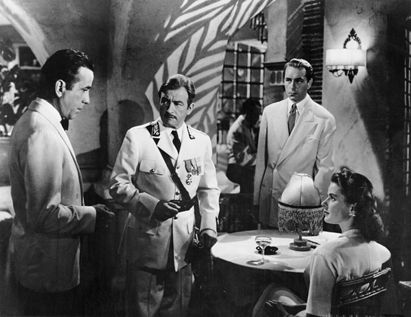 Rick Blain (Humphrey Bogart), Captain Renault (Claude Rains), Victor Lazlo (Paul Henreid), and Ilsa Lund (Ingrid Bergma) meet in in Rick's Café Américain.
