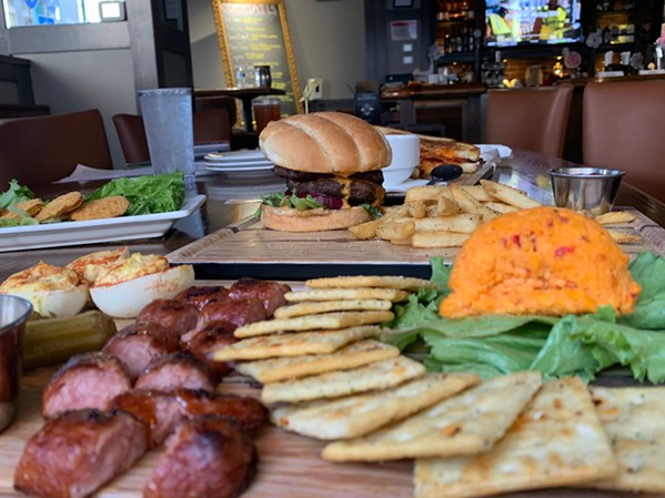 King & Union Bar Grocery's Charcuterie Board sits in front of the KU Burger