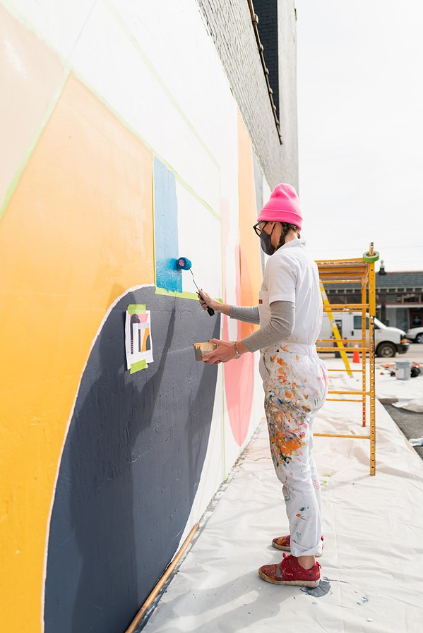 Erin Miller Wray works on her Memphis mural on the side of the old Ambassador Hotel, which is the future home of South of Beale gastropub. - NLA PROJECTS