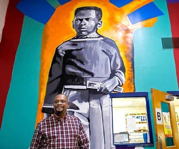 Harry Williams, one of three students who integrated Bruce Elementary in 1961, in front of his image in Bullock's mural. - JAMOND BULLOCK