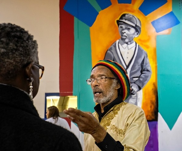 Menelik Fombi, one of three students who integrated Bruce Elementary in 1961, in front of his image in Bullock's mural. - JAMOND BULLOCK
