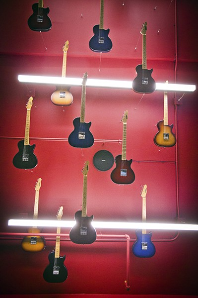The ceiling of the hallway leading to the museum's second-floor space is lined with guitars that point the way to the exhibits. - JUSTIN FOX BURKS