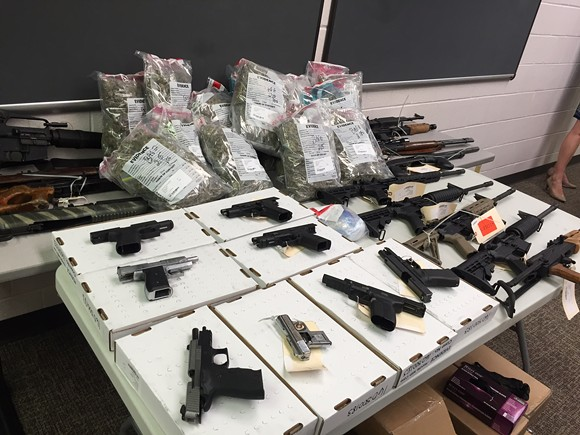The guns and drugs on this table were associated with one investigation that involved three homes.