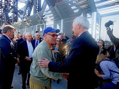 Memphis congressman Steve Cohen and Arkansas Governor Asa Hutchinson engage in a ceremonial handshake midway on the new pedestrian/bike pathway across the Harahan Bridge. Looking on at left are Scott Moore of Union Pacific Railroad, project founder Charles McVean and Charlie Newman, counsel to the project. - JB
