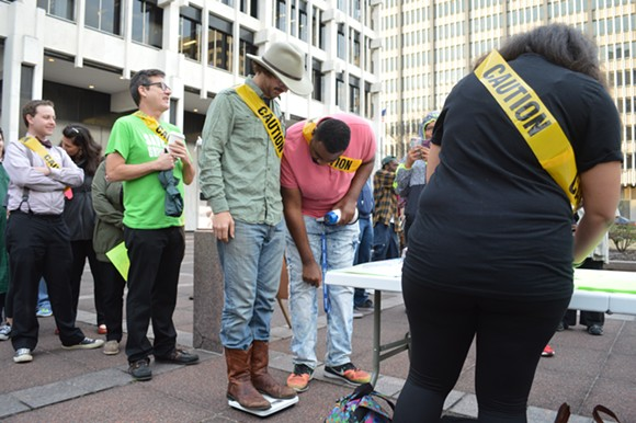 Brandon Taylor steps on a provided scale to be weighed-in, a gesture meant to poke fun at MPD's gathered intel for those listed as requiring poilce escort when entering City Hall. - MICAELA WATTS