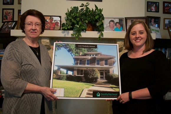 Sr. Maureen Griner and Tracy Burgess of the Dorothy Day House hold a photo of  one of three former Church Health properties they will buy and renovate for the families they serve. The mantle behind them showcases families who came in homeless, and left with employment and housing. - MICAELA WATTS