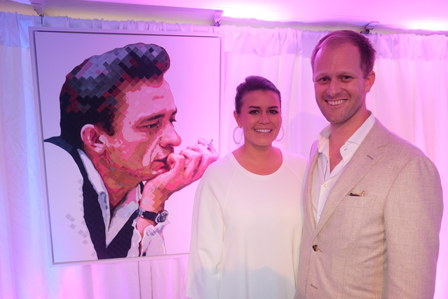 Charlie Hanavich, with his wife, Helen, and his Johnny Cash portrait at The Grand Auction.