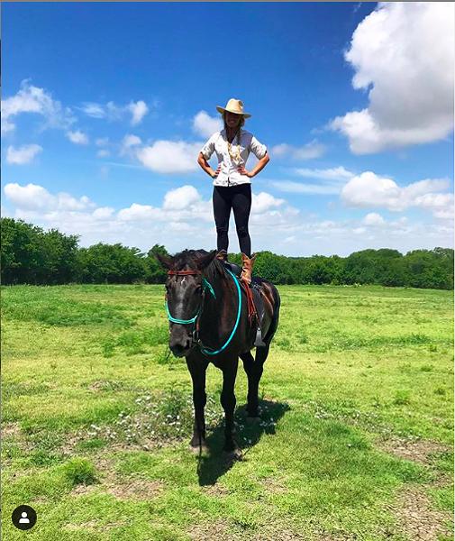 Slaver stands on a horse. - JENNY SLAVER/INSTAGRAM