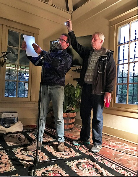 Dennis Lynch provides illumination as Scott Banbury reads out the names of Groundwater Control Board members. - JACKSON BAKER
