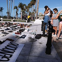 People look at hundreds of pairs of shoes displayed at the Capitol to pay tribute to Hurricane Maria's victims after a research team led by Harvard University estimated that 4,645 people lost their lives, a number not confirmed by the government, in San Juan, Puerto Rico, June 1, 2018.