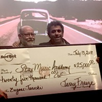 Director Eugene Jarecki (right) presents a check for $25,000 to the Stax Music Academy, represented by Tim Sampson (left). The money came from the sale of Elvis Presley's Rolls Royce, which was used in the new documentary film The King.