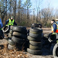 Volunteers stacking collected tires at T.O. Fuller Park
