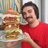 "Ryan Joseph Hopgood of Memphis Sandwich Clique loves sandwiches. He's holding a ""Dagwood"" style sandwich The Green Beetle made up for fun. Note: They don't sell these at The Green Beetle."