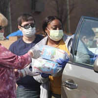 Volunteers load food into a car at a mobile food pantry