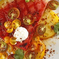 Grilled watermelon salad with goat cheese, tomatoes, and honey-lime vinaigrette