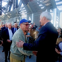Memphis congressman Steve Cohen and Arkansas Governor Asa Hutchinson engage in a ceremonial handshake midway on the new pedestrian/bike pathway across the Harahan Bridge. Looking on at left are Scott Moore of Union Pacific Railroad, project founder Charles McVean and Charlie Newman, counsel to the project.