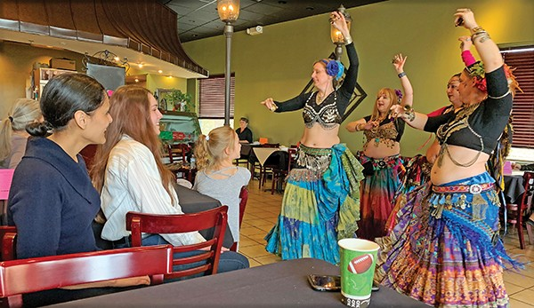 House District 97 candidate Gabby Salinas (l), one of two Democrats running, enjoys an exotic Mideastern dance in her honor at a weekend fundraiser. - JACKSON BAKER