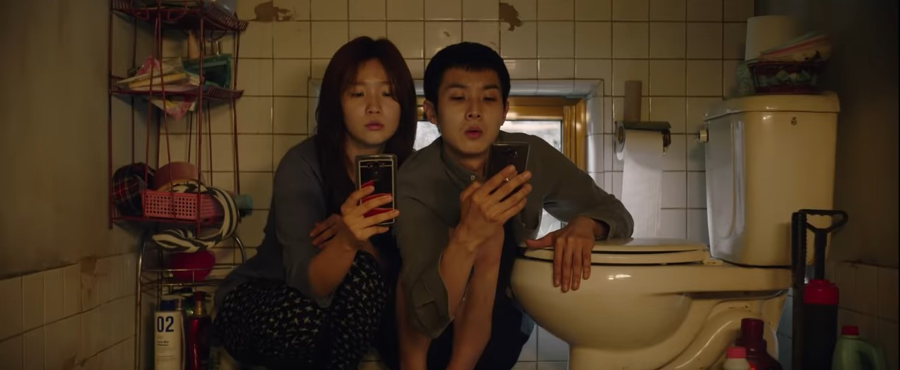 Park So-dam and Choi Woo-shik search for free wifi in the bathroom of their basement apartment.