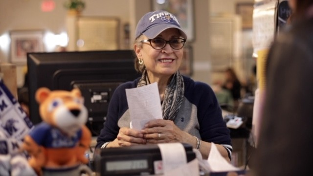 Suhair Lauck at her post behind the cash register in the documentary The Little Tea Shop. - COURTESY OF LAST BITE FILMS.