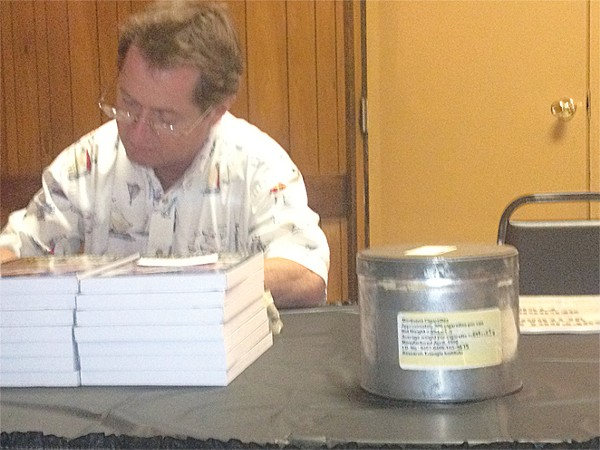 Irvin Rosenfeld signs copies of his book with one of his U.S. cannabis supply cans nearby.