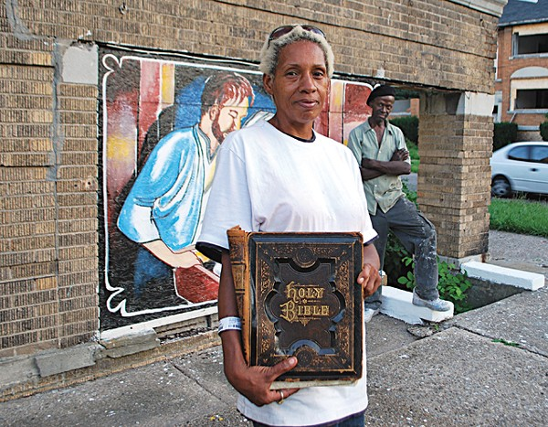 Kathina Carey, with sign painter Leon Goodin in the background, stands by the apartment building that she made into her canvas.