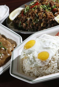 Lumpia sariwa (fresh vegetable eggroll topped with peanut garlic sauce), left, sisig (crispy pork with ginger sauce on sizzling hot plate), upper right, and tap-silog (marinated sirloin with garlic fried rice topped with fried eggs), front, from New Lutong Pinoy in Madison Heights