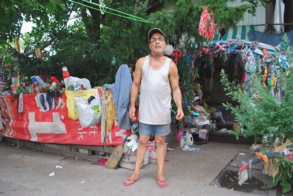 Migo stands in front of his home art exhibit.
