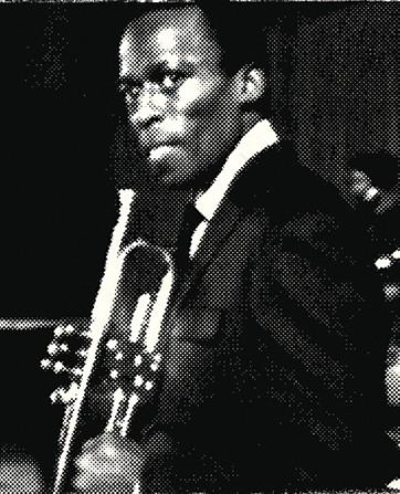 Miles Davis holds his horn.