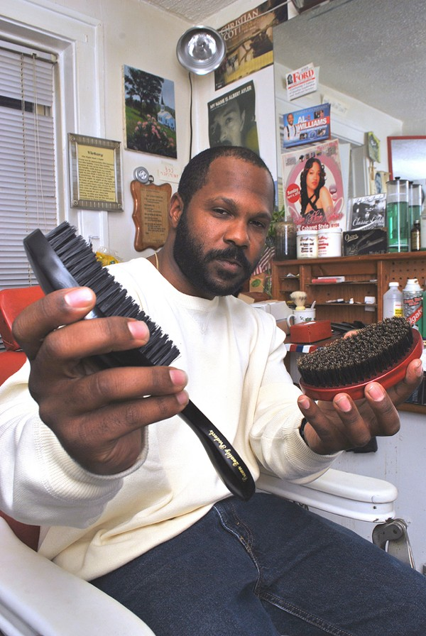 Robert Watson with his brushes in his home barbershop.