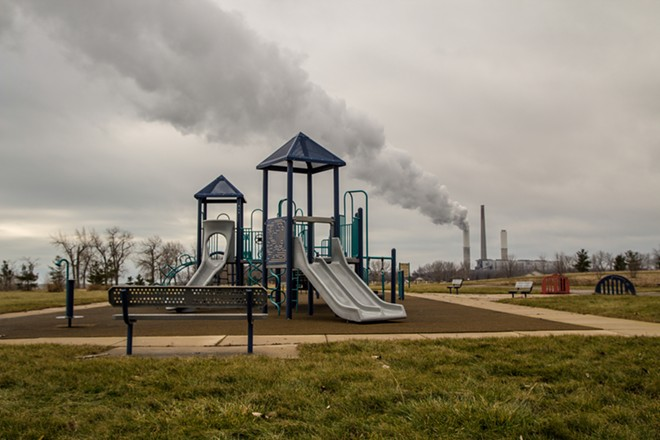 Playground in William C. Sterling State Park with billowing smokestack in the background. - SHUTTERSTOCK