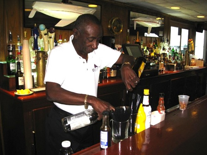 Jerome Adams mixing his signature drink behind the bar at Bayview Yacht Club in 2011. - PHOTO BY MICHAEL JACKMAN