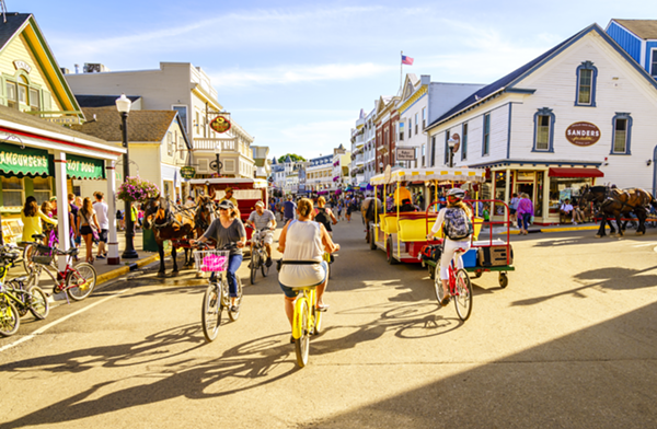 People ride bikes through on Market Street on Mackinac Island. - SHUTTERSTOCK